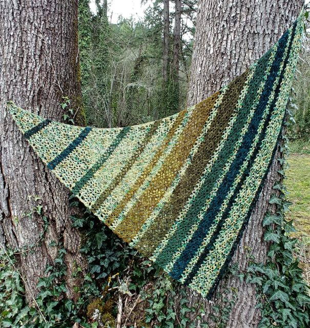 Ned's Dye-Pot triangular Shawl with speckled yarn alternated with solid minis in varying widths of stripes.