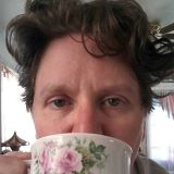 profile pic of C. Jane Peaking over a floral tea cup